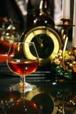 Vidrio de vino con el coñac en decoraciones de los christmass Foto de archivo libre de regalías