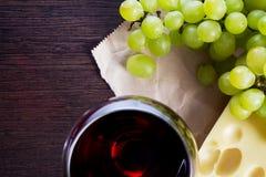 Vidrio de vino con las uvas y el pedazo de copia-espacio del queso Imagenes de archivo