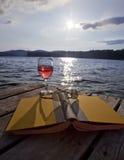 Vidrio de vino, de libro, y de vidrios en el lago Imagen de archivo libre de regalías