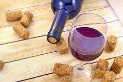 Vidrio de vino en el fondo de botellas y de corchos Foto de archivo