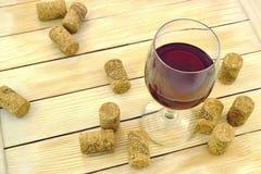 Vidrio de vino en el fondo de corchos y de listones de madera Imagenes de archivo