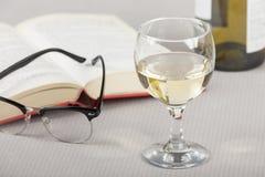 Vidrio de vino en una tabla con un libro abierto Fotografía de archivo