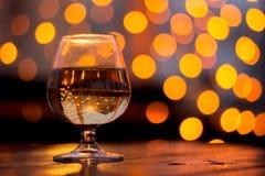 Vidrio de vino en una tabla en el fondo de un bokeh amarillo Foto de archivo