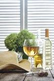 Vidrio de vino que se coloca en la tabla con el sombrero de paja imagen de archivo