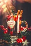 Vidrio de vino reflexionado sobre con Feliz Navidad festiva de la decoración y del texto en el fondo del bokeh Fotos de archivo libres de regalías