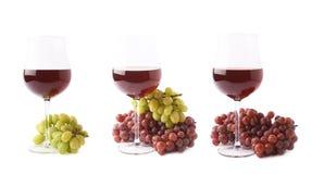 Vidrio de vino rojo al lado de una rama de uvas Imagen de archivo libre de regalías