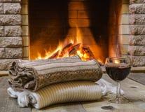 Vidrio de vino rojo antes de la chimenea Imagen de archivo libre de regalías