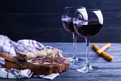 Vidrio de vino rojo con el salami y el grissini Fotografía de archivo libre de regalías