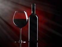 Vidrio de vino rojo con la botella Fotos de archivo