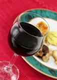 Vidrio de vino rojo con la comida Imagen de archivo libre de regalías