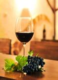 Vidrio de vino rojo con la uva Fotos de archivo libres de regalías
