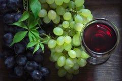 Vidrio de vino rojo con la uva madura en un fondo de madera Cierre para arriba Fotografía de archivo libre de regalías