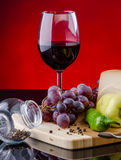Vidrio de vino rojo con la uva y las verduras Imágenes de archivo libres de regalías