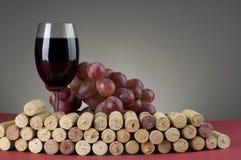 Vidrio de vino rojo con la uva y los corchos. Fotografía de archivo libre de regalías
