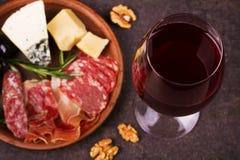 Vidrio de vino rojo con queso, el prosciutto y el salami Vida del vino y todavía del queso Foto de archivo