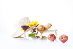 Vidrio de vino rojo, de uvas y de queso aislados en blanco Imagen de archivo