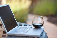 Vidrio de vino rojo en la computadora portátil Foto de archivo