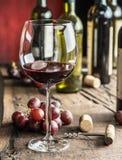 Vidrio de vino rojo en la tabla Botella y uvas de vino en los vagos imagen de archivo