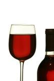 Vidrio de vino rojo que se coloca al lado de la botella de vino - aislada encendido Foto de archivo libre de regalías