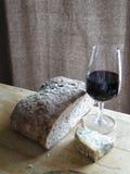 Vidrio de vino rojo, queso verde Fotos de archivo libres de regalías