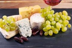 Vidrio de vino rojo, servido con las uvas y el queso Imagenes de archivo