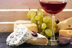 Vidrio de vino rojo, servido con las uvas y el queso Imagen de archivo