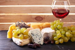 Vidrio de vino rojo, servido con las uvas y el queso Foto de archivo