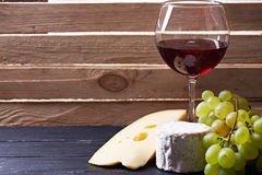 Vidrio de vino rojo, servido con las uvas y el queso Foto de archivo libre de regalías