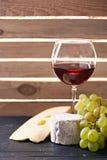 Vidrio de vino rojo, servido con las uvas y el queso Fotografía de archivo libre de regalías