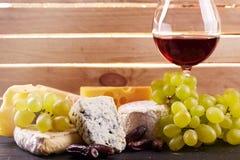 Vidrio de vino rojo, servido con las uvas y el queso Fotos de archivo libres de regalías