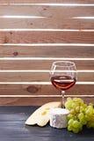 Vidrio de vino rojo, servido con las uvas y el queso Fotos de archivo