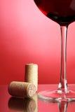 Vidrio de vino rojo y de corchos Imágenes de archivo libres de regalías