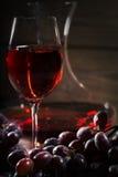 Vidrio de vino rojo y un manojo de uvas Fotos de archivo libres de regalías