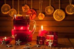 Vidrio de vino y de las decoraciones reflexionados sobre de la Navidad, velas, regalos foto de archivo