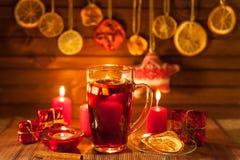 Vidrio de vino y de las decoraciones reflexionados sobre de la Navidad, velas, regalos imagen de archivo