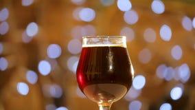 Vidrio de vueltas de la cerveza oscura lentamente alrededor de su eje Las burbujas de la cerveza suben a la espuma de la cerveza almacen de metraje de vídeo