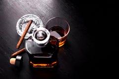 Vidrio de whisky con el cigarro que fuma Fotografía de archivo libre de regalías