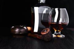 Vidrio de whisky con el cigarro que fuma Foto de archivo libre de regalías