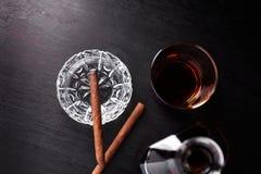 Vidrio de whisky con el cigarro que fuma whisky, tabaco Fotos de archivo libres de regalías