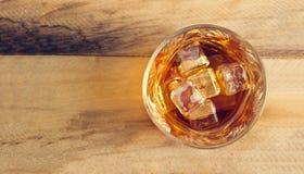 Vidrio de whisky con hielo en el fondo de madera, visión superior Foto de archivo