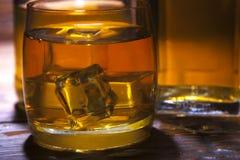 Vidrio de whisky con hielo en un fondo de madera Imagenes de archivo