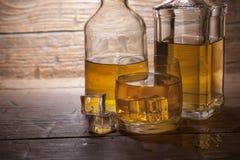 Vidrio de whisky con hielo en un fondo de madera Foto de archivo libre de regalías