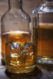 Vidrio de whisky con hielo en un fondo de madera Fotografía de archivo
