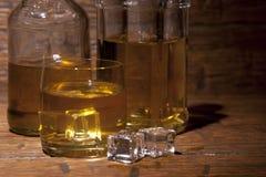 Vidrio de whisky con hielo en un fondo de madera Fotos de archivo