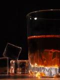 Vidrio de whisky con hielo en un fondo de madera Fotos de archivo libres de regalías