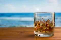 Vidrio de whisky con hielo en una tabla de madera contra el mar Fotos de archivo