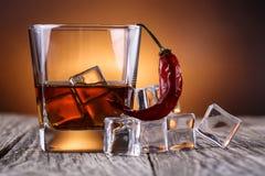Vidrio de whisky con hielo y el chile Imagen de archivo libre de regalías