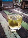 Vidrio de whisky con los cubos de hielo en la tabla de madera del vintage Fotos de archivo libres de regalías