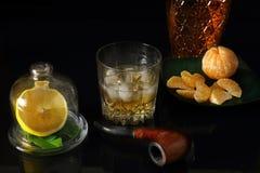 Vidrio de whisky con un tubo que fuma y una jarra Fotografía de archivo