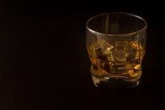 Vidrio de whisky contra un fondo oscuro Foto de archivo libre de regalías